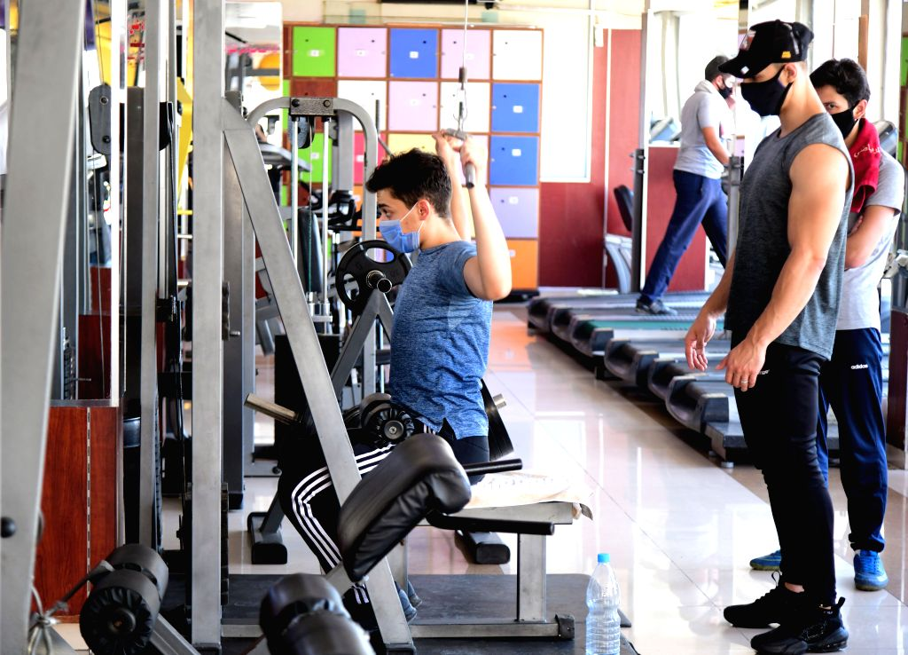 People wearing face masks work out at a gym in Damascus, capital of Syria, on Aug. 30, 2020. In Syria, 75 new cases were detected on Sunday, raising the overall ...