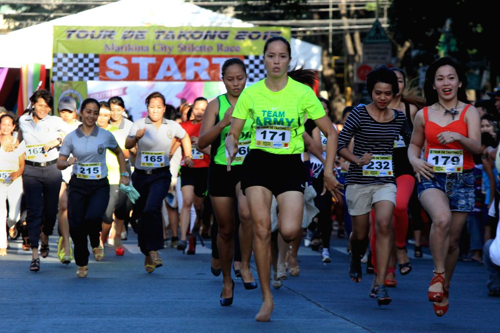 "People wearing high-heeled shoes run during the ""Tour de Takong"" (Tour of High Heels) in Marikina City, the Philippines, Nov. 14, 2015. Residents ..."