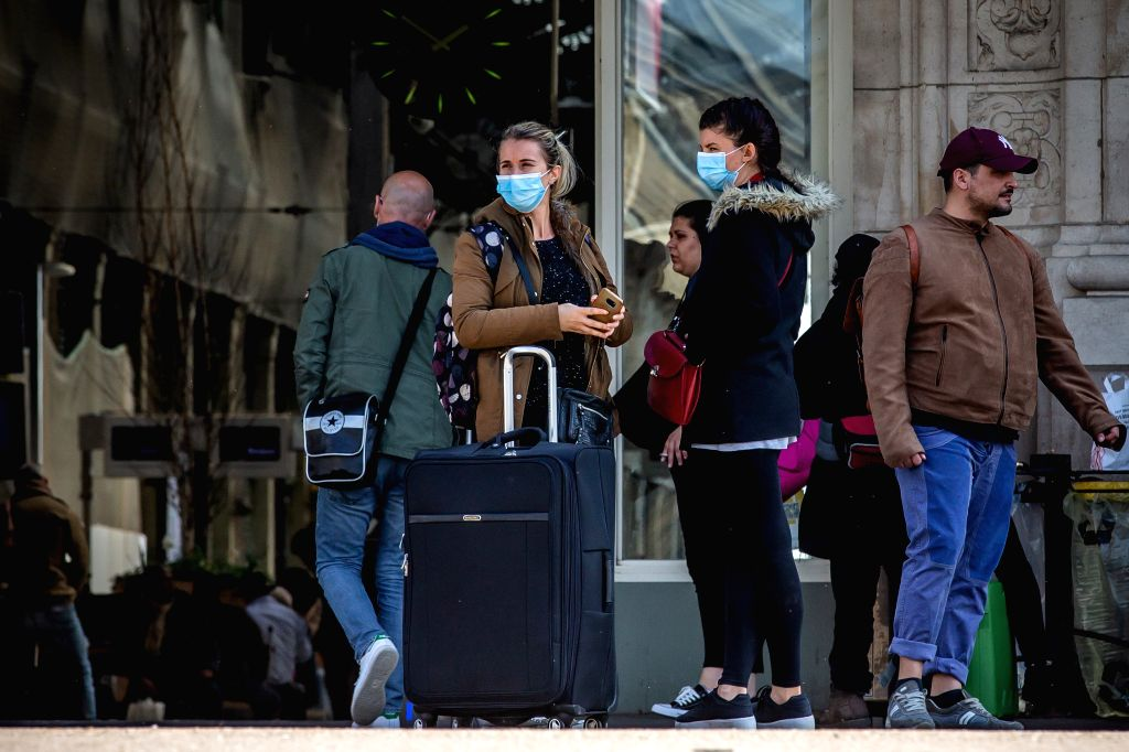 People wearing masks are seen at the Gare de Lyon train station in Paris, France, March 19, 2020. One hundred and eight COVID-19 patients died in 24 hours in France, ...