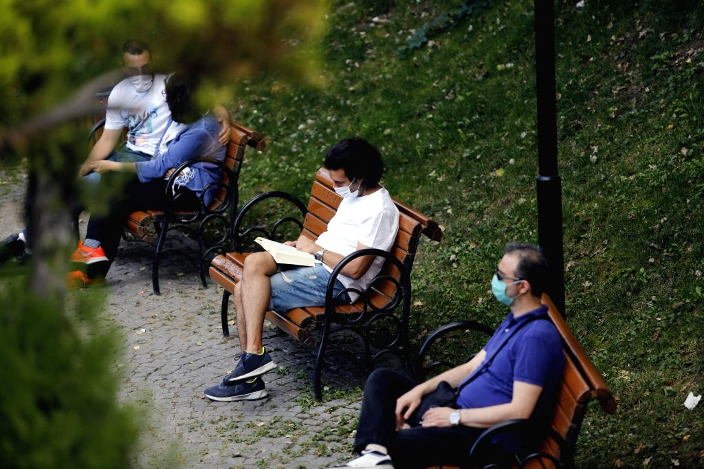 People wearing masks are seen on benches at a park in Ankara, Turkey, on Sept. 20, 2020. The country's daily COVID-19 cases increased by 1,519 on Sunday, raising ...