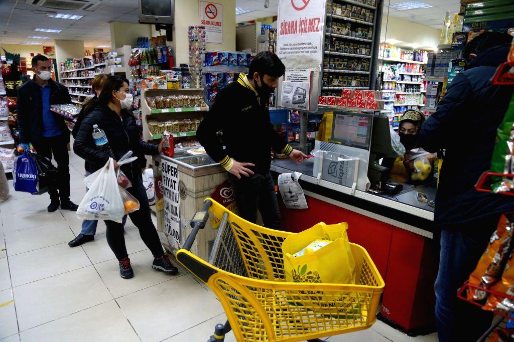 People wearing masks do shopping at a convenience store in Ankara, Turkey, on May 8, 2020. Turkish Health Minister Fahrettin Koca on Friday reported 1,848 new COVID-19 ... - Fahrettin Koca