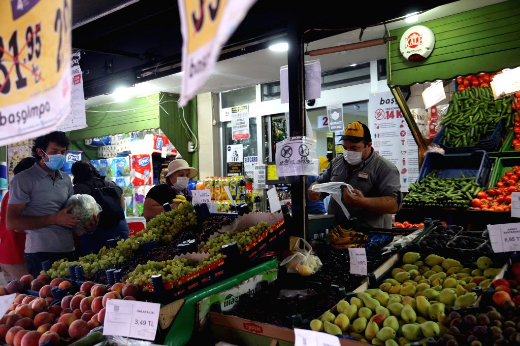 People wearing masks select fruits at a stall in Ankara, Turkey, on Aug. 12, 2020. Turkey confirmed 1,212 new COVID-19 cases on Wednesday, raising the total ...