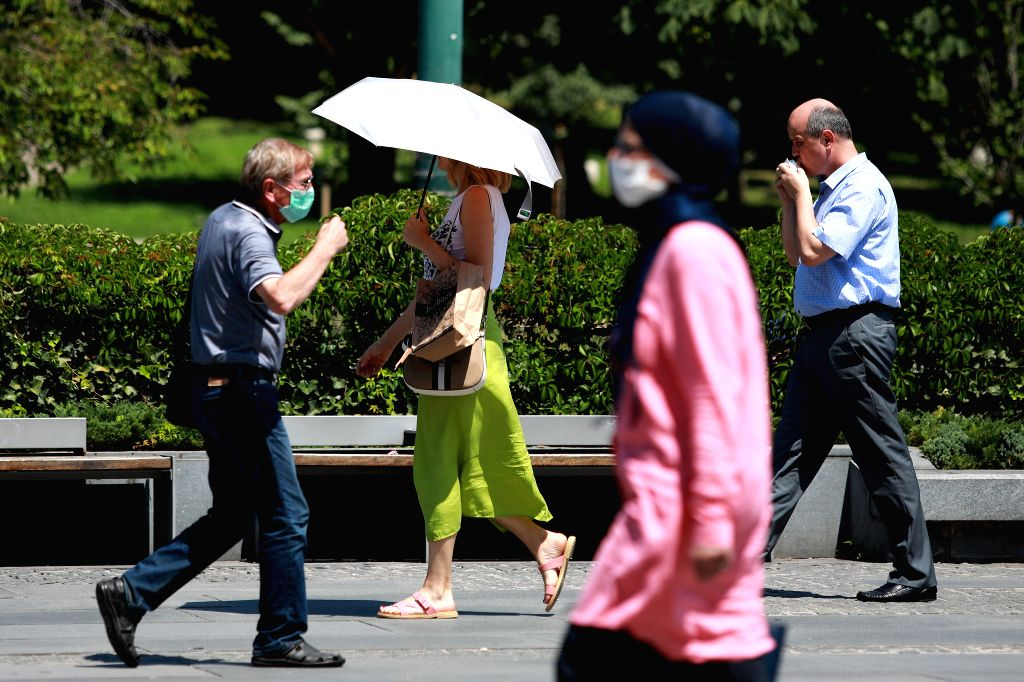 People wearing masks walk in a street in Sarajevo, Bosnia and Herzegovina (BiH), July 30, 2020. According to the report of the Federal Hydrometeorological ...