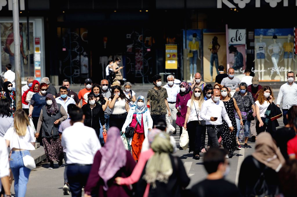 People wearing masks walk on a street in Ankara, Turkey on July 8, 2020. Turkey's COVID-19 cases increased by 1,041 on Wednesday, while the total cases climbed to ... - Fahrettin Koca