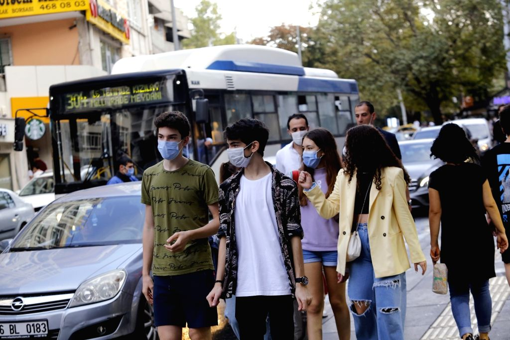 People wearing masks walk on a street in Ankara, Turkey, on Sept. 20, 2020. The country's daily COVID-19 cases increased by 1,519 on Sunday, raising the total ...