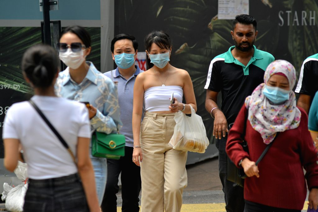 People wearing masks walk on a street in Kuala Lumpur, Malaysia, March 9, 2020. Malaysia on Monday announced 18 new cases of COVID-19, bringing the total ...