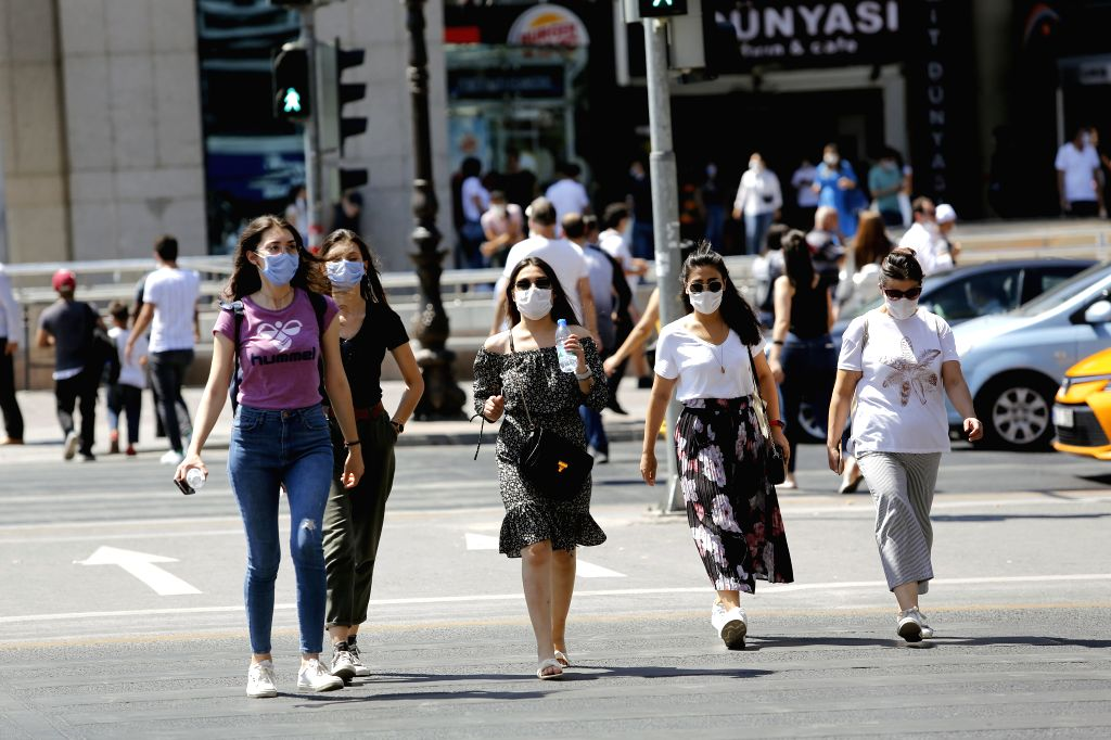 People wearing masks walk on the street in Ankara, Turkey, on Aug. 7, 2020. Turkey reported 1,185 new COVID-19 cases on Friday, raising the total diagnosed cases to ... - Fahrettin Koca