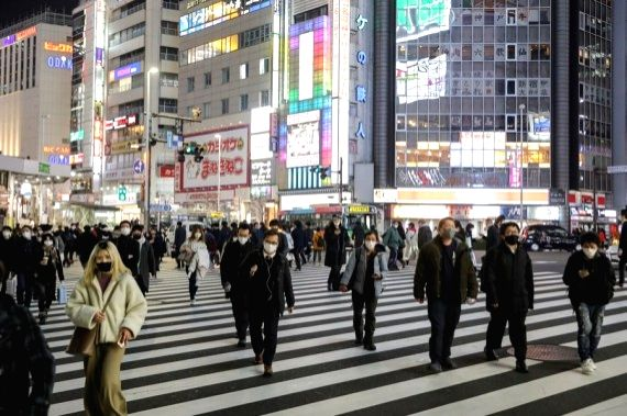 People wearing masks walk on the street in Tokyo, Japan, Jan. 22, 2021.