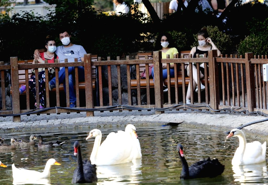 People wearing masks watch swans at a park in Ankara, Turkey, on Sept. 11, 2020. Turkey confirmed 1,671 new COVID-19 cases on Friday, raising the total diagnosed ...