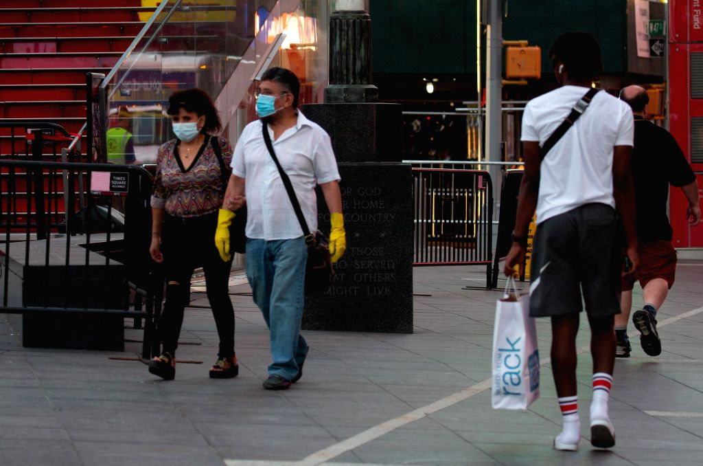 People wearing personal protective equipment walk on Times Square in New York, the United States, June 25, 2020. The number of COVID-19 cases in the United States ...