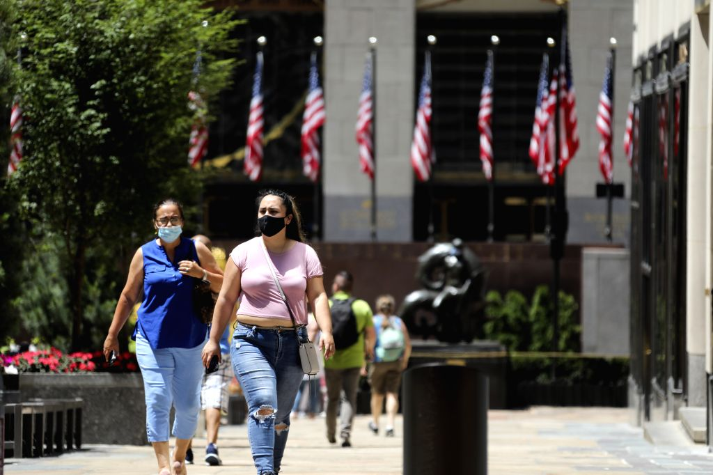 People with face masks walk on Fifth Avenue in New York, the United States, July 4, 2020. The number of COVID-19 cases in the United States topped 2.8 million on ...