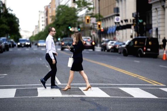 People without mask cross a road in Washington, D.C., the United States, May 14, 2021.