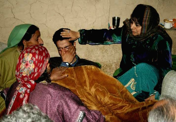 Peoples Democratic Party (PDP) chief Mehbooba Mufti Sayeed with the family of the the sarpanch who was killed by militants in Awantipora of Jammu and Kashmir on April 18, 2014.