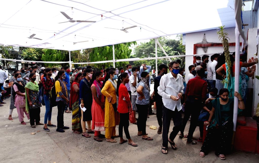 Peoples ignoring social distance stand in a queue to register their names for COVID-19 tests, amid a countrywide spike in coronavirus cases, at a government health center, in Patna on Sunday, ...