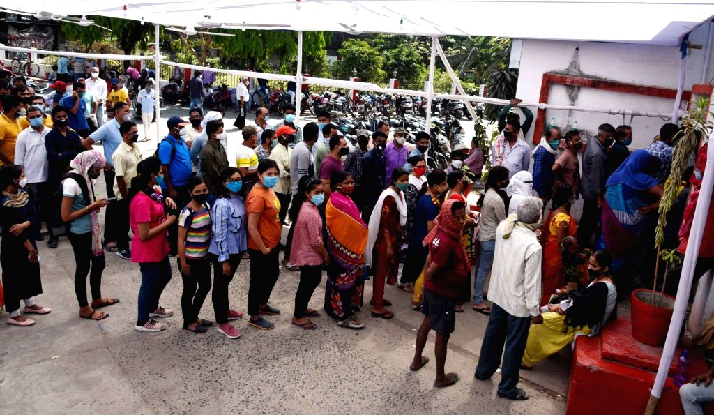 Peoples ignoring social distance stand in a queue to register their names for COVID-19 tests, amid a countrywide spike in coronavirus cases, at New Gardiner Road government health center, in ...