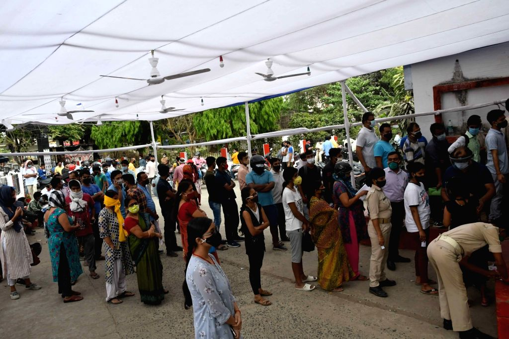 Peoples wait stand in a queue to register their names for COVID-19 tests, amid a countrywide spike in coronavirus cases, at a government health center, in Patna On Thursday, 22 April, 2021.