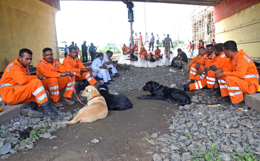 Personnel involved in the rescue operations at the 40-year-old Majerhat Bridge, a portion of which collapsed a day earlier, take rest, in Kolkata on Sept 5, 2018. A part of the bridge ...