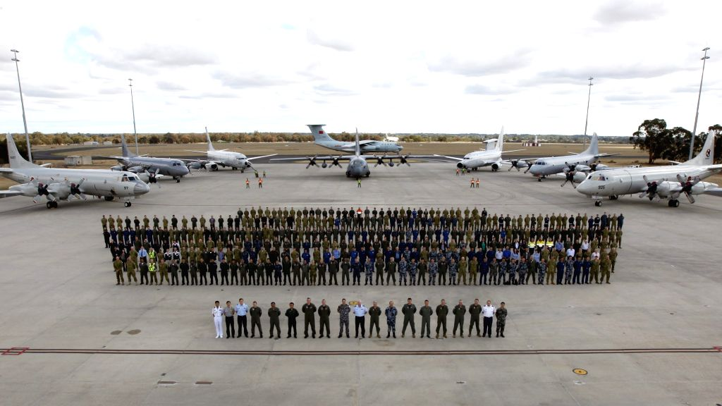 In this photo released by Australian Defence Department, personnel and multinational aircrafts involved in the search of MH370 in Southern Indian Ocean pose for ... - Tony Abbott