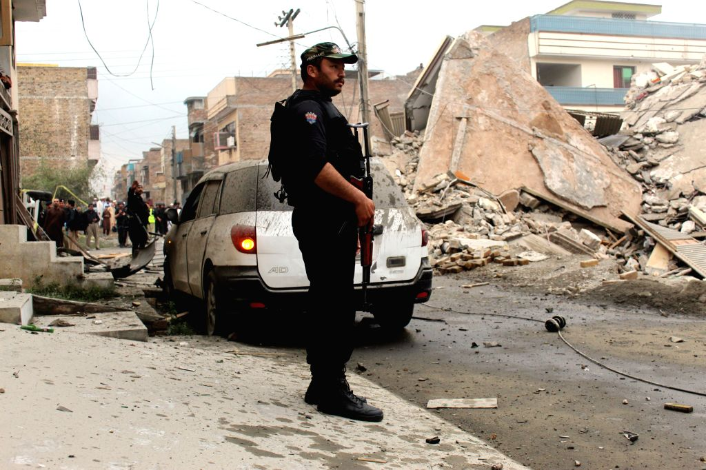 PESHAWAR, April 16, 2019 (Xinhua) -- A policeman stands guard near a destroyed militant hideout during an operation against insurgents in Peshawar, northwest Pakistan, April 16, 2019. At least six people including a policeman and five militants were