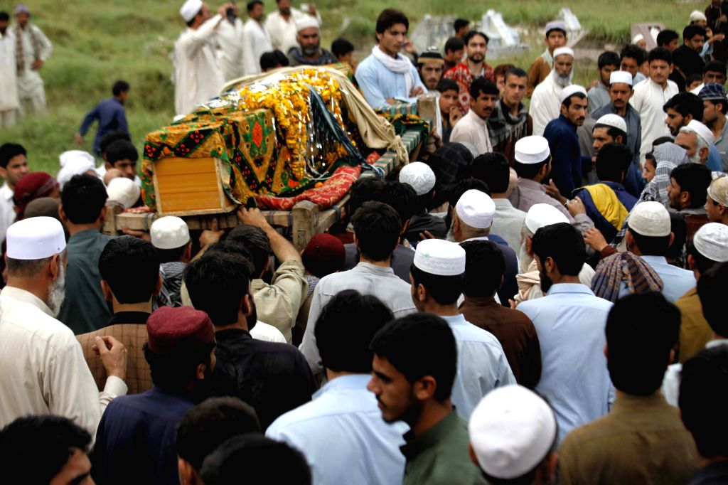 Pakistani people attend a funeral ceremony of victims killed in heavy rain and wind in northwest Pakistan's Peshawar, April 27, 2015. At least 30 people were ...