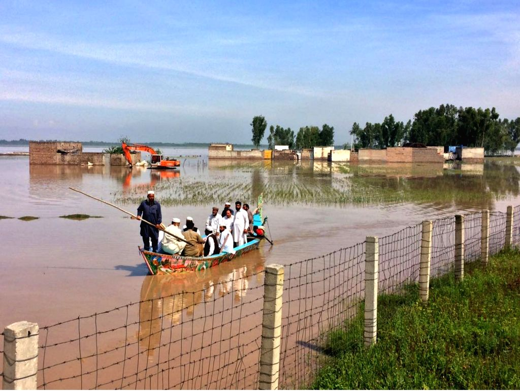 PESHAWAR, April 4, 2016 - Pakistani people ride on a boat through a flooded street following heavy rain on the outskirts of northwest Pakistan's Peshawar, April 4, 2016. At least 65 people were ...