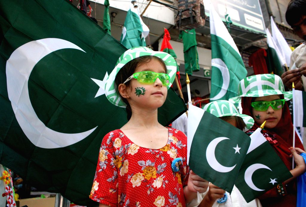 PESHAWAR, Aug. 13, 2016 - Pakistani children hold national flags on a street on the eve of the country's Independence Day in northwest Pakistan's Peshawar on Aug. 13, 2016. Pakistan will celebrate ...