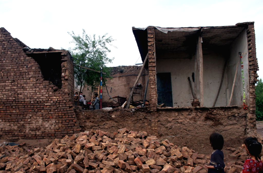 Children look at a destroyed house after rain storm in northwest Pakistan's Peshawar on Aug. 16, 2014. At least 18 people were killed and more than 100 injured as .
