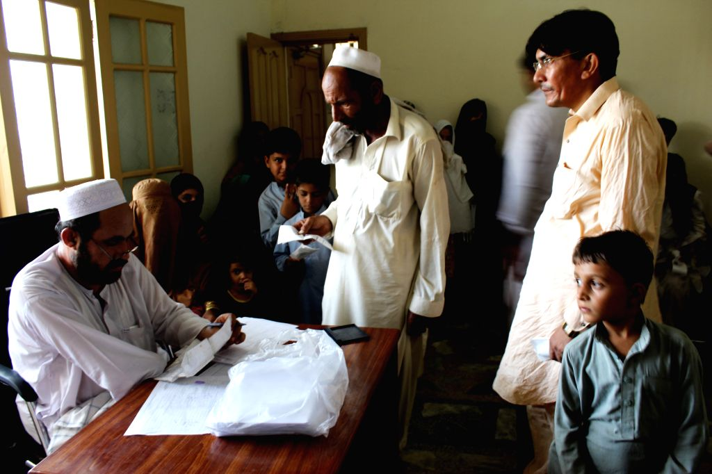 PESHAWAR, Aug. 18, 2017 - A Pakistani official (1st L) checks documents of Afghan refugees at a Pakistani registration centre on the outskirts of northwest Pakistan's Peshawar, Aug. 18, 2017. ...