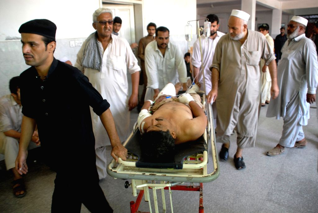 PESHAWAR, Aug. 3, 2016 - People transfer an injured man to a hospital in northwest Pakistan's Peshawar, Aug. 3, 2016. At least four people were injured in an explosion that took place near a police ...