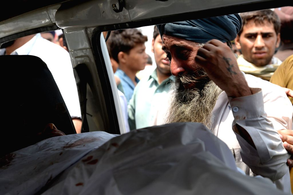 Pakistani minority Sikhs mourns beside a body during a protest against the killing of a colleague in northwest Pakistan's Peshawar on Aug. 6, 2014. A Sikh trader ...