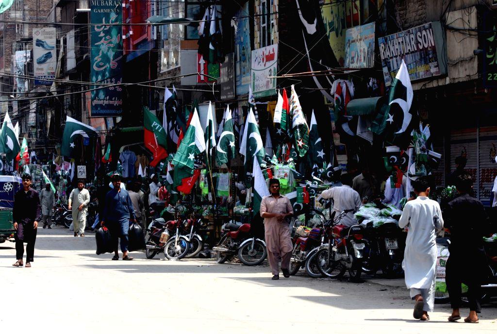 PESHAWAR, Aug. 8, 2017 - People visit stalls to buy Pakistan's national flags in northwest Pakistan's Peshawar, Aug. 8, 2017. Pakistan will celebrate Independence Day on Aug. 14.