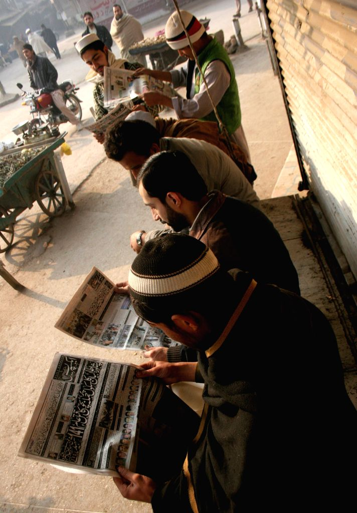 People read newspaper reporting a militant attack on an army-run school in northwest Pakistan's Peshawar on Dec. 17, 2014. A total of 141 people, including 132 ...