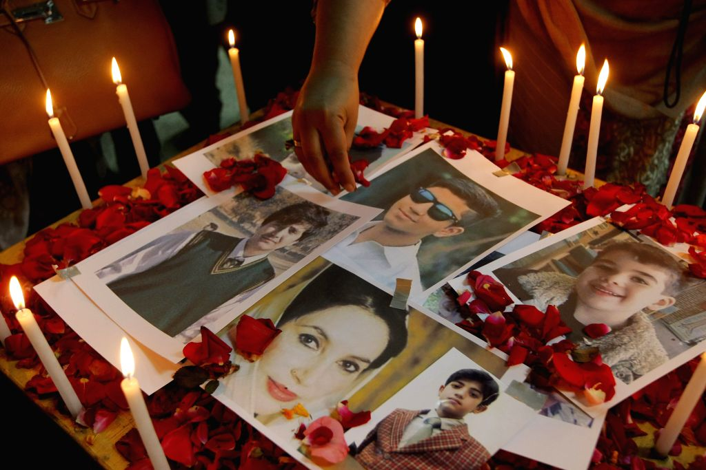 A Pakistani woman puts rose petals over the photos of victims of the militant attack on the army-run school during a tribute ceremony in northwest Pakistan's ...