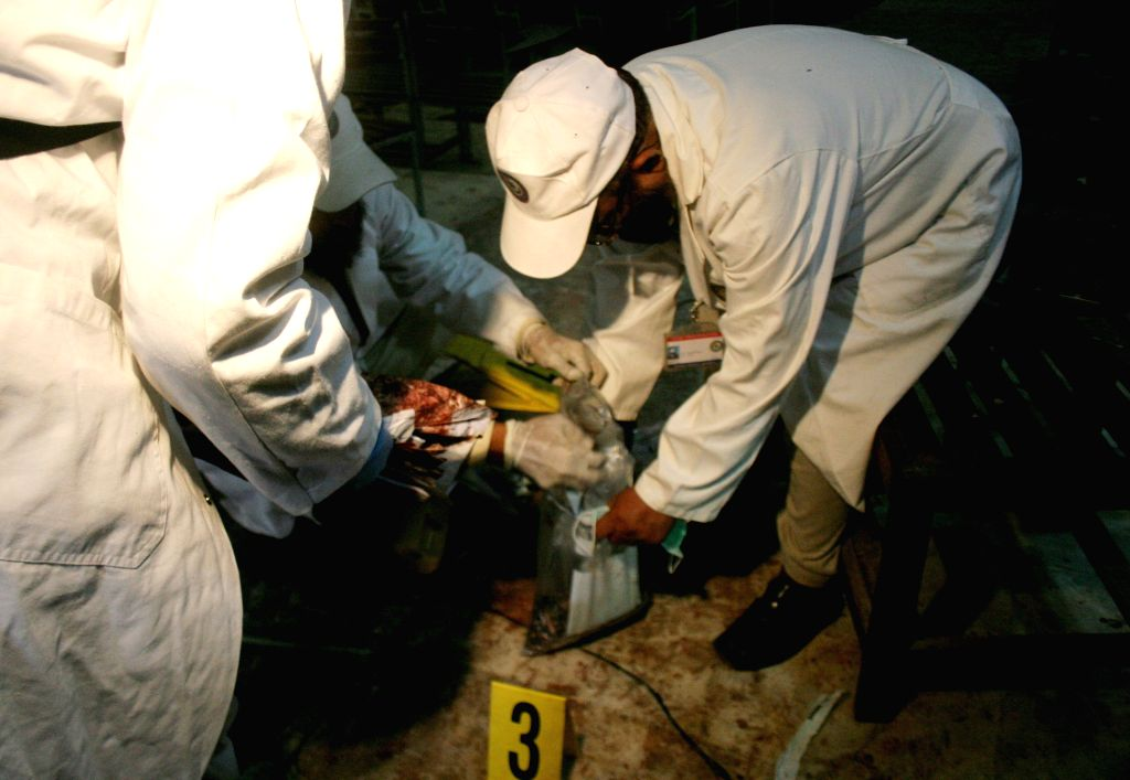 Pakistani investigators collect evidence at the site of the militants' attack on the army-run school in northwest Pakistan's Peshawar, Dec. 18, 2014. At least 141 .