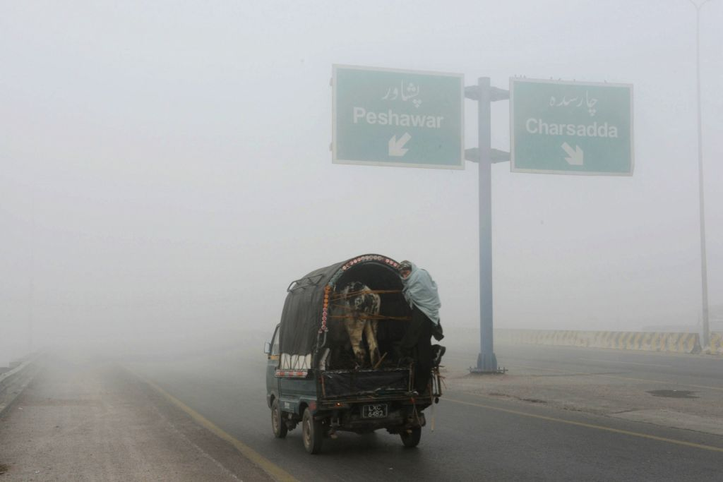 A vehicle moves along a road during a foggy day in northwest Pakistan's Peshawar on Dec. 19, 2013. The ongoing spell of dense fog weather has continued ..