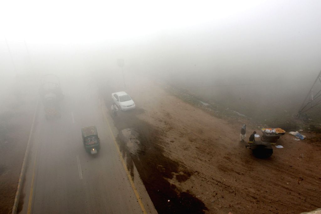 Vehicles move along a road during a foggy day in northwest Pakistan's Peshawar on Dec. 19, 2013. The ongoing spell of dense fog weather has continued to .