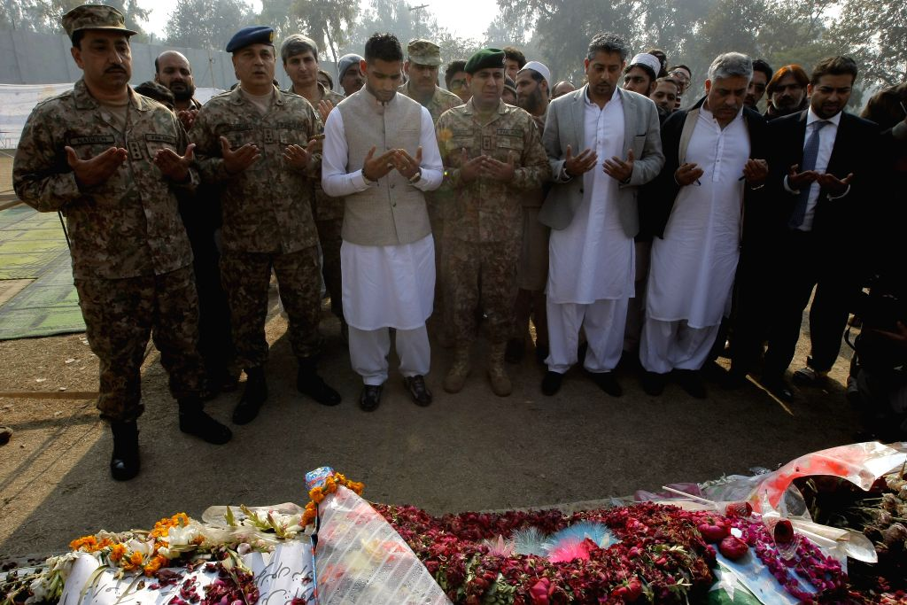 British boxer Amir Khan (3rd L, front) prays with Pakistani military officials at a memorial in the army-run school where 150 people were massacred by the Taliban .