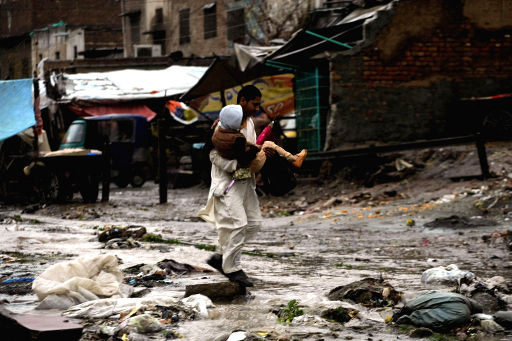 A man carries a child as he crosses a waterlogged street after heavy rain in northwest Pakistan's Peshawar, Feb. 25, 2015. At least two women were killed as a roof ...