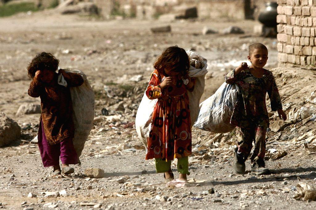 Pakistani girls collect garbage in a street on the outskirts of northwest Pakistan's Peshawar, Feb. 25, 2015. (Xinhua/Umar Qayyum)