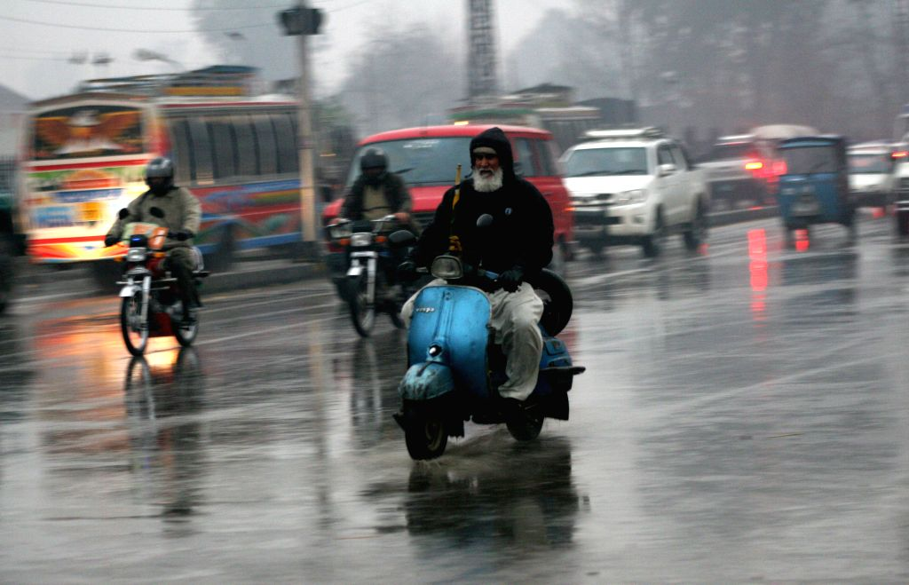 Vehicles move on a road during winter rain in northwest Pakistan's Peshawar, Jan. 13, 2015.