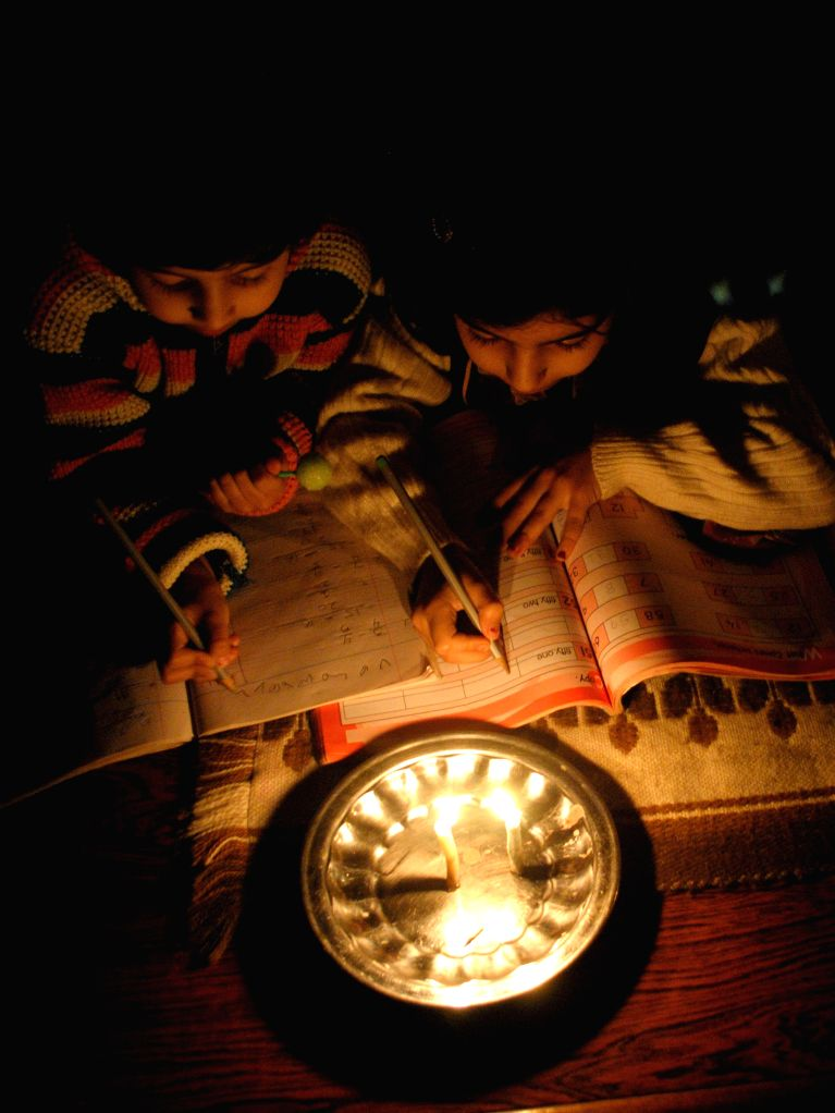 Pakistani children study in candle light during a power cut in northwest Pakistan's Peshawar on Jan. 25, 2015. An apparent rebel attack on a key power line plunged