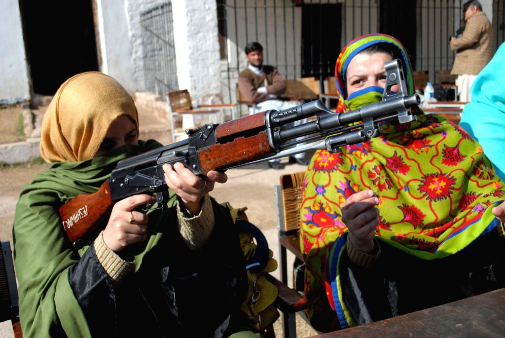 A female teacher holds an AK-47 during a weapons training session in northwest Pakistan's Peshawar on Jan. 27, 2015. A month after terrorist attack on a army-run ..