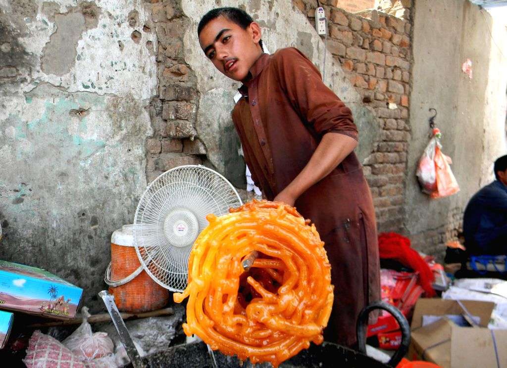 """PESHAWAR, July 2, 2016 - A vendor fries sweet snacks locally called """"Jalebi"""" at a stall during the fasting month of Ramadan in northwest Pakistan's Peshawar, July 2, 2016."""