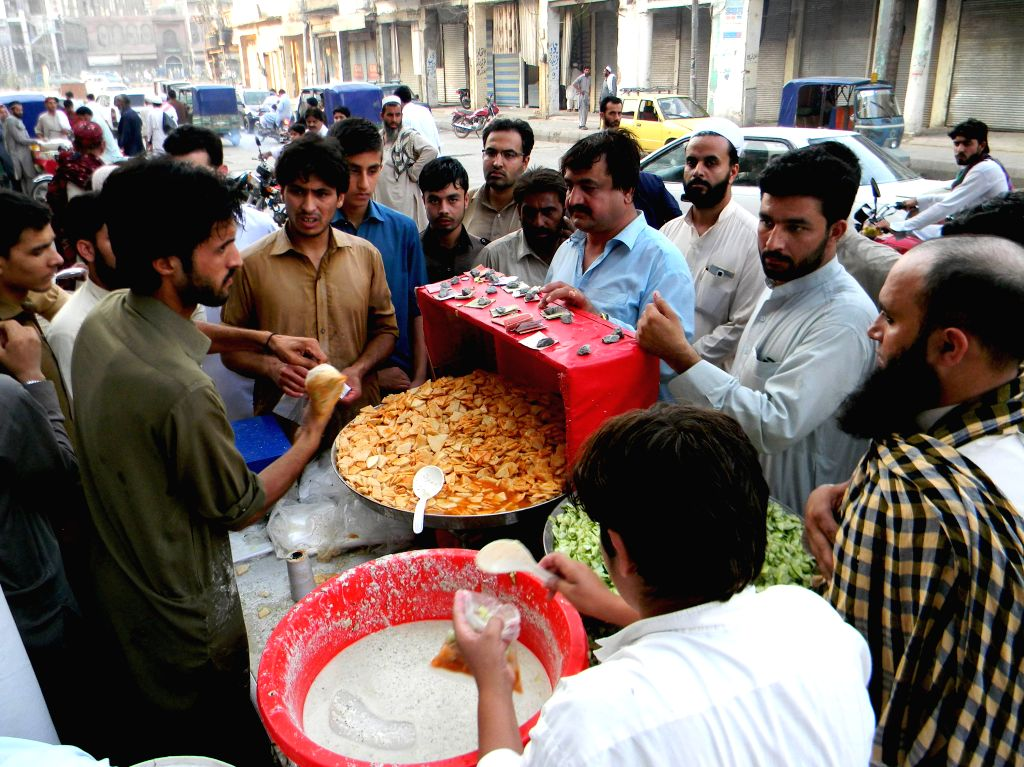 PESHAWAR, July 2, 2016 - People buy food for Iftar, the evening meal during the Islamic month of Ramadan, at a stall in northwest Pakistan's Peshawar, July 2, 2016.