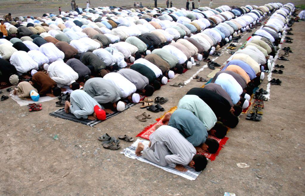 Afghan refugees offer Eid al-Fitr prayers on the outskirts of northwest Pakistan's Peshawar, on July 28, 2014. Muslims around the world celebrate the Eid al-Fitr ..