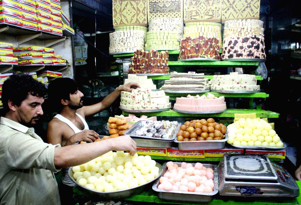 PESHAWAR, July 5, 2016 - People arrange traditional sweets at a bakery ahead of Eid al-Fitr festival in Pakistan's northwest Peshawar on July 5, 2016. Eid al-Fitr, a major Muslim holiday, marks the ...
