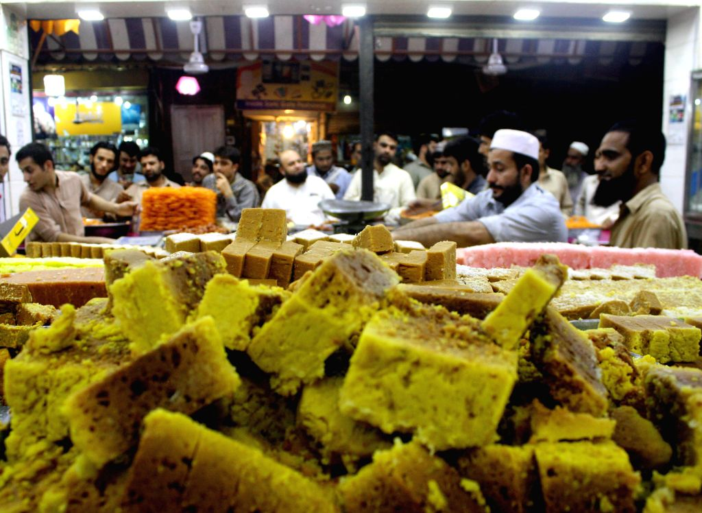 PESHAWAR, July 5, 2016 - People buy traditional sweets at a bakery ahead of Eid al-Fitr festival in Pakistan's northwest Peshawar on July 5, 2016. Eid al-Fitr, a major Muslim holiday, marks the end ...