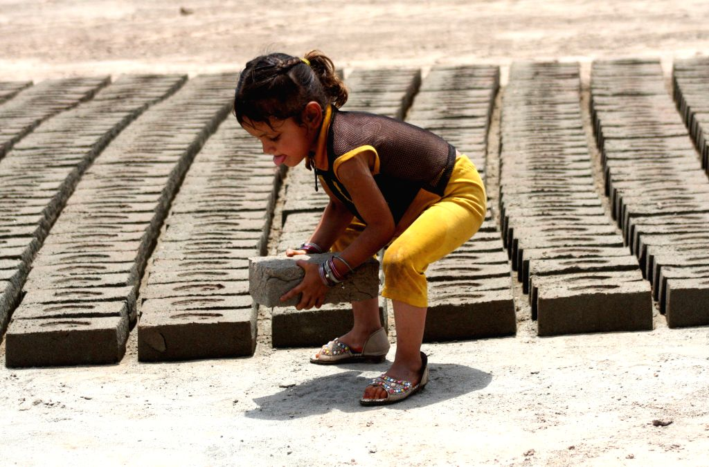 PESHAWAR, June 12, 2019 - A girl works at a brick factory on the outskirts of Peshawar, Pakistan, on June 12, 2019. The World Day Against Child Labor is observed every year on June 12.