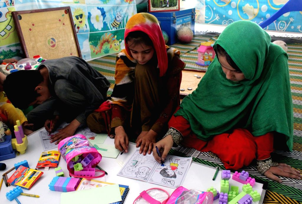 PESHAWAR, June 19, 2017 - Afghan children draw pictures at the office of the United Nations High Commissioner for Refugees (UNHCR) registration center ahead of the World Refugee Day, in northwest ...