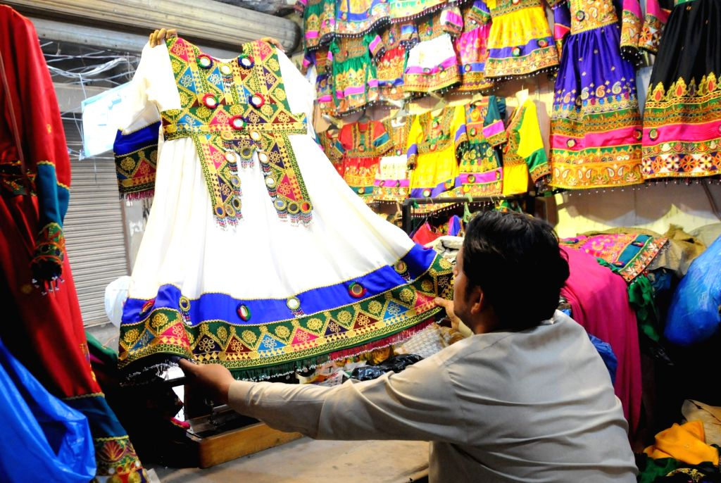 PESHAWAR, June 4, 2019 - A shopkeeper displays a traditional dress ahead of Eid al-Fitr festival in northwest Pakistan's Peshawar on June 3, 2019.